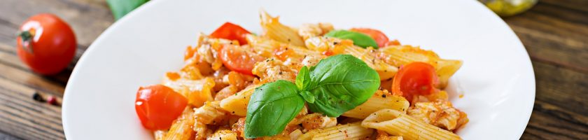Penne pasta in tomato sauce with chicken, tomatoes, decorated with basil on a wooden table. Italian food. Pasta Bolognese.