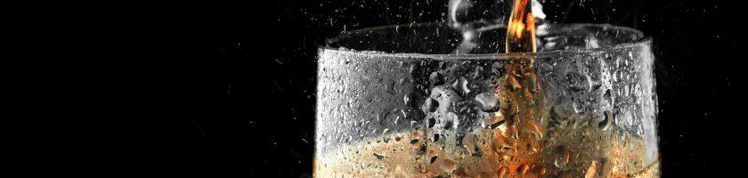 Soft drink glass with ice splash on dark background.