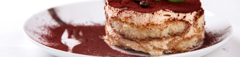 Tiramisu, traditional Italian Dessert on a white plate.On a Marble Background.Copy space. selective focus.